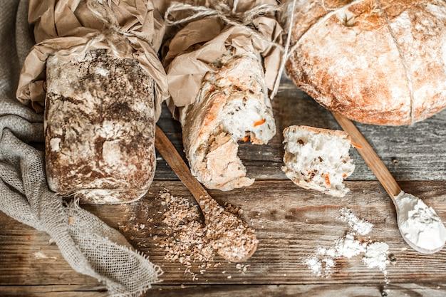 焼きたてのパンと古い木製の背景に木のスプーン 無料写真