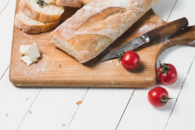 Fresh bread with knife on cutting board Free Photo