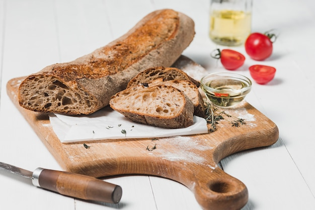 Fresh bread with knife on cutting board Free Photo