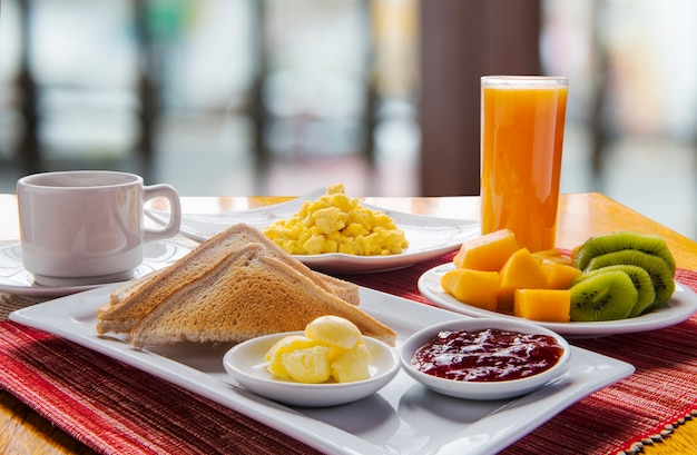 Fresh and bright continental breakfast table with fruit plate. Premium Photo
