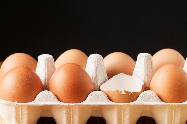 Fresh brown  eggs in box  on black background Premium Photo