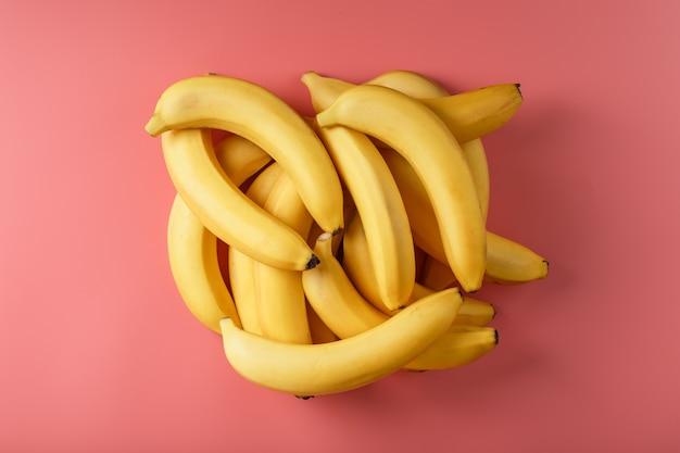 ピンクの背景に分離された黄色いバナナの新鮮な束。ミニマルなコンセプト。フリースペース Premium写真
