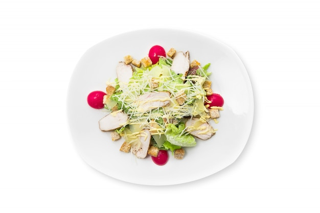 Fresh caesar salad with chicken on a white plate isolated. Premium Photo