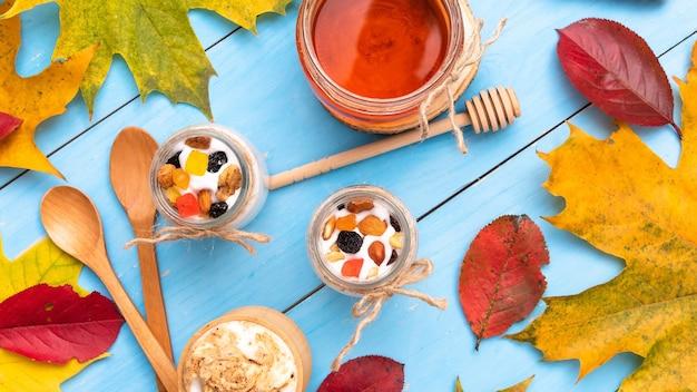 秋のテーブルにヨーグルトと木製カップの新鮮なカプチーノ。 Premium写真