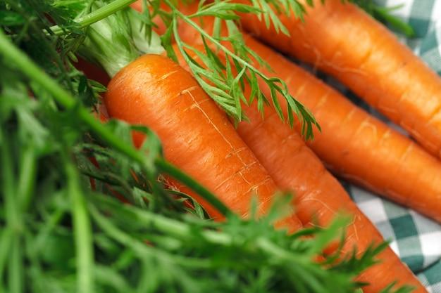 Fresh carrots on checkered tablecloth Premium Photo