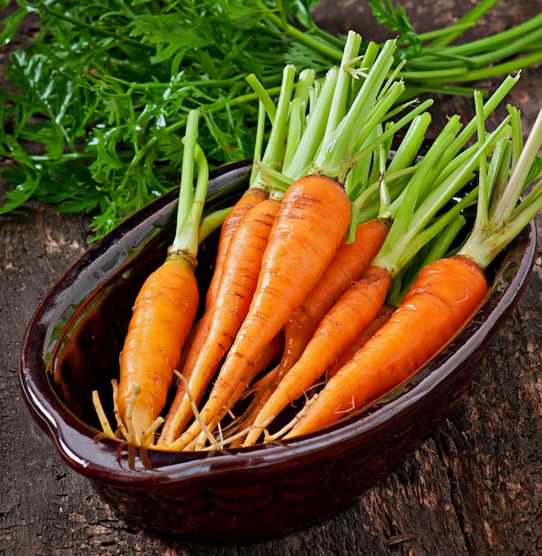 Fresh carrots on old wooden surface Free Photo