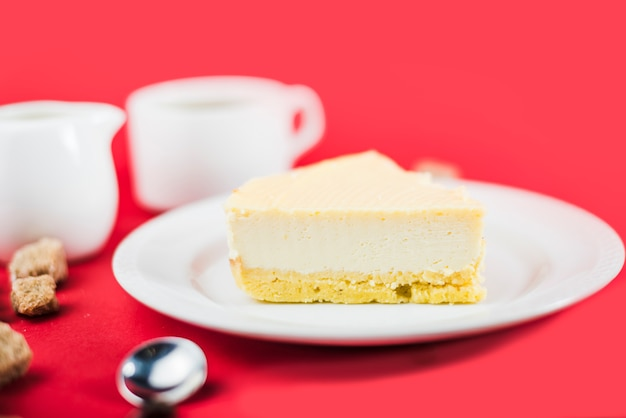 Fresh cheese cake on white plate against red background Free Photo