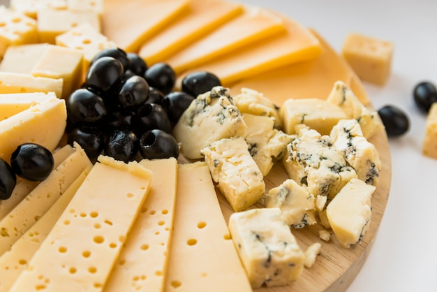 Fresh cheese and olives on chopping board Free Photo