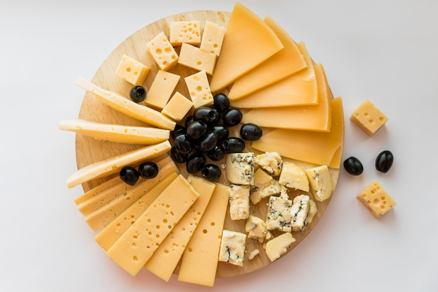 Fresh cheese and olives on wood chopping board Free Photo