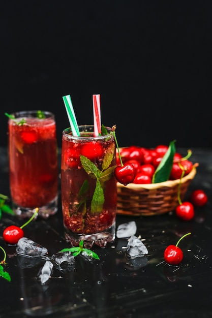 Fresh cherries placed in a basket and black cherries with water splashes Premium Photo