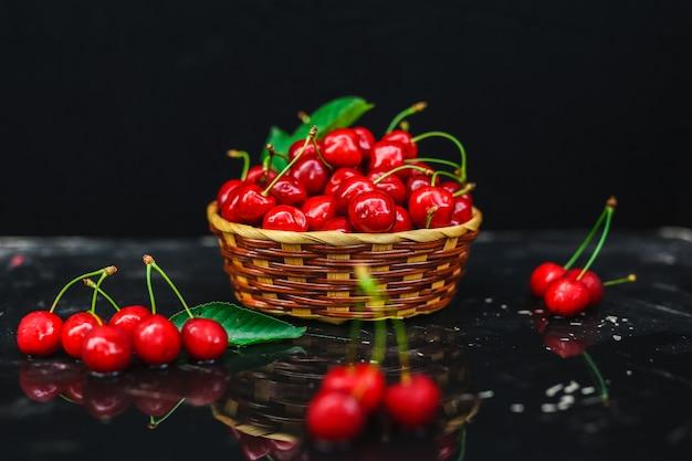 Fresh cherries placed in a basket Premium Photo