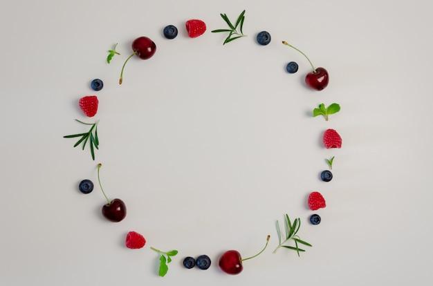 Fresh cherry, blueberry, raspberry, mint and rosemary leaf Premium Photo
