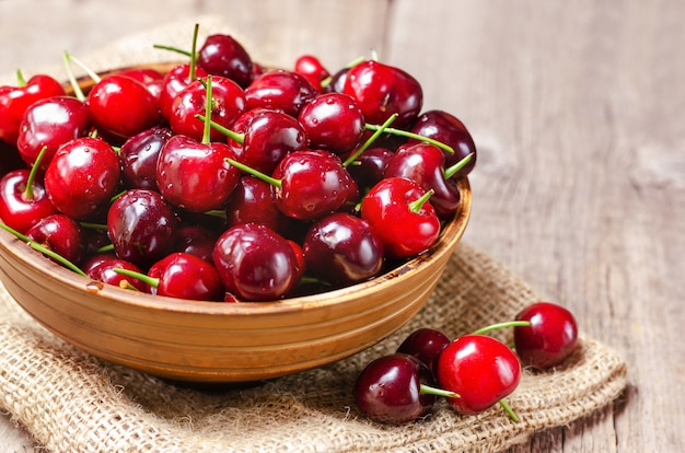 Fresh cherry in a clay bowl. Premium Photo