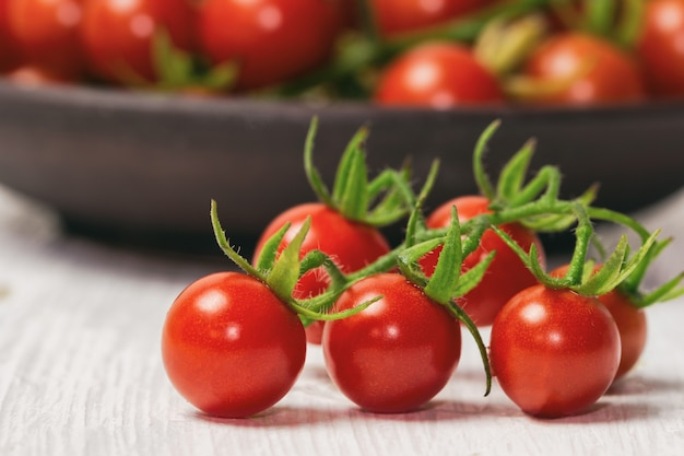 Fresh cherry tomato on white wood table. Premium Photo