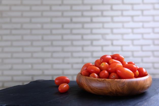 Fresh cherry tomatoes on bowl wooden with white wall. Premium Photo