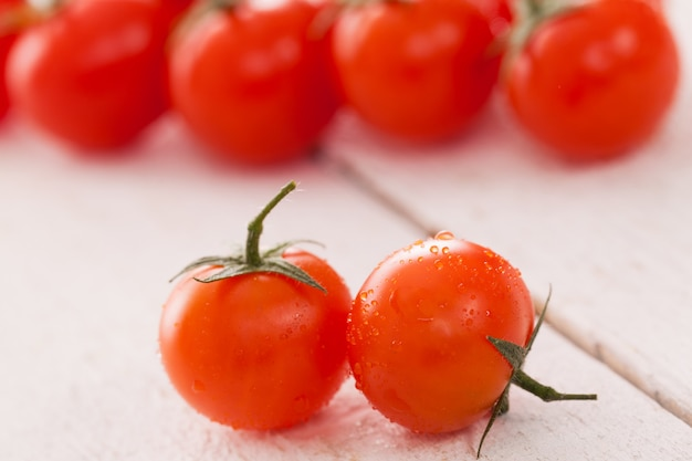 Fresh cherry tomatoes on a white surface Free Photo