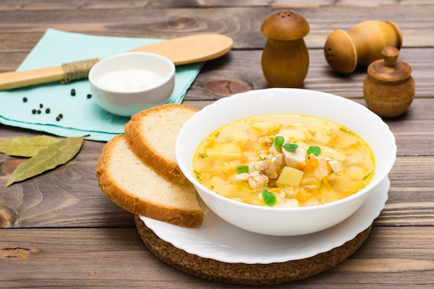 Fresh chicken broth soup with potatoes and herbs in a white bowl on a wooden table Premium Photo