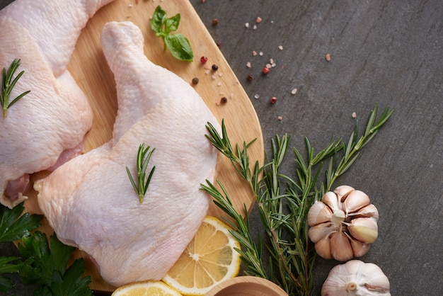 Fresh chicken meat portions for cooking and barbecuing with fresh seasoning. raw uncooked chicken leg on cutting board. Free Photo