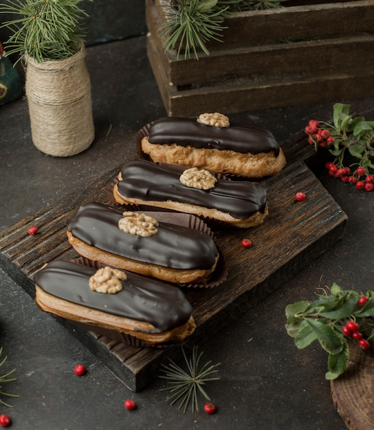 Fresh chocolade eclairs with walnut on wooden board Free Photo