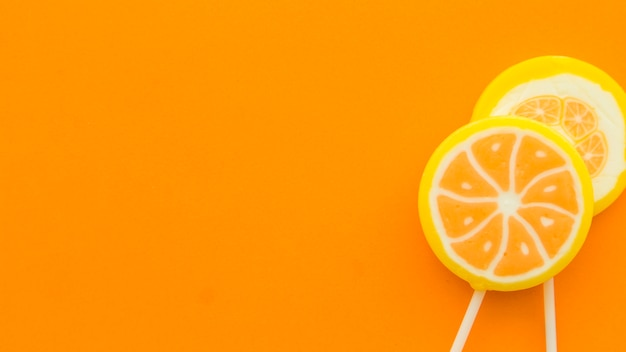 Fresh citrus fruit lollipops on orange backdrop Photo | Free