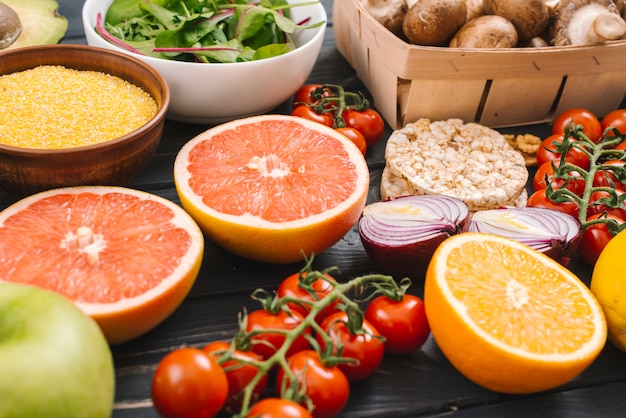 Fresh citrus fruits; vegetables and puffed rice cake on wooden desk Free Photo
