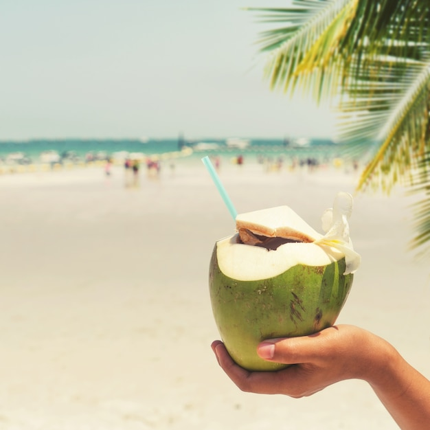 Fresh coconut cocktails with in woman hands on tropical beach - vacation in summer. vintage color styles Premium Photo