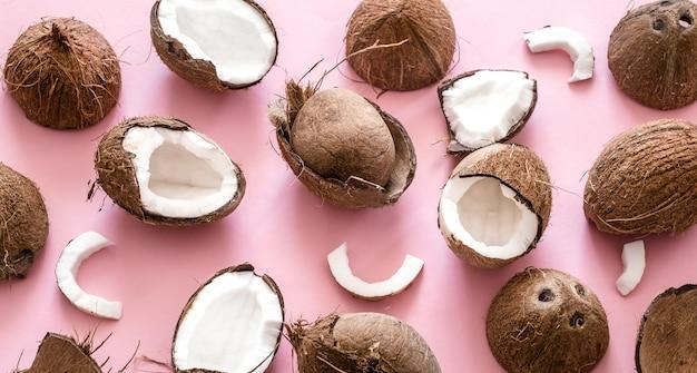 Свежие половинки кокоса на розовом фоне, дизайн в стиле поп-арт. вид сверху, крупный план, креативная концепция Бесплатные Фотографии