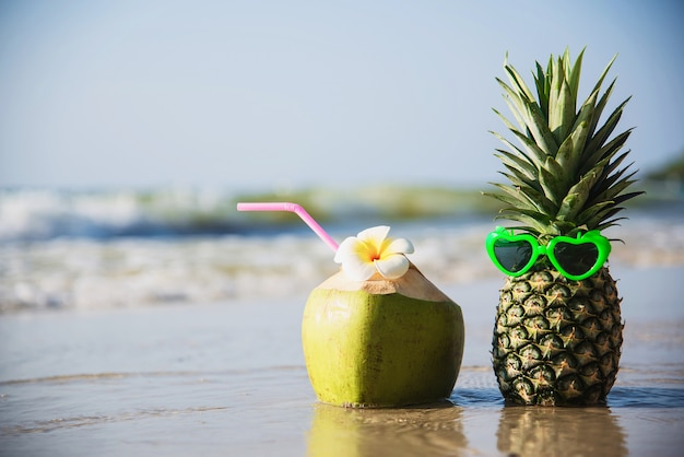 Fresh coconut and pineapple put sun lovely glasses on clean sand beach with sea wave - fresh fruit with sea sand sun vacation concept Free Photo