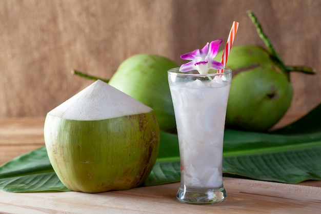 Fresh coconut water in a glass on a wooden board for drinking Premium Photo