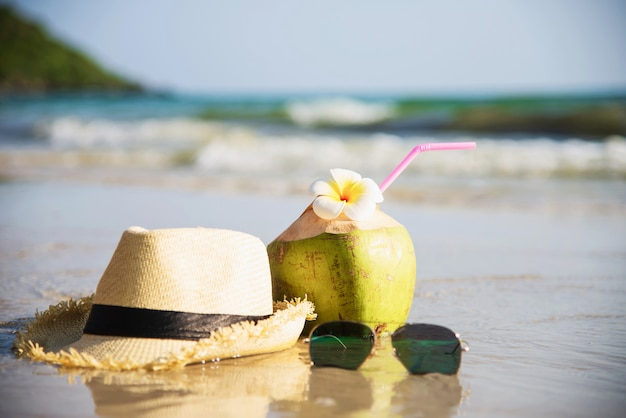 Fresh coconut with hat and sun glasses on clean sand beach with sea wave - fresh fruit with sea sand sun vacation concept Free Photo