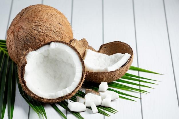 Свежие кокосы положить на белый деревянный фон Бесплатные Фотографии