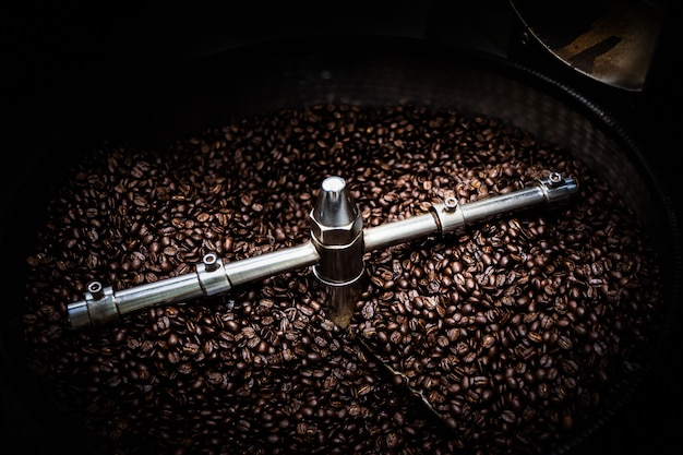 Fresh coffee beans and roasted spinning cover professional machine close up photo blur and dark background long exposure shot movement concept Premium Photo