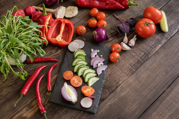 Fresh colorful vegetables from a kitchen garden on a dark wooden background Premium Photo