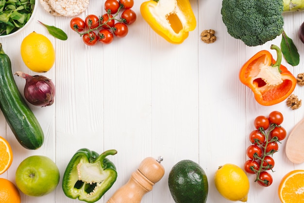 Fresh colorful vegetables; fruits and pepper shakers on white wooden desk Free Photo