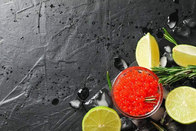 Свежая композиция с икрой и цитрусовыми на черном столе, вид сверху Premium Фотографии