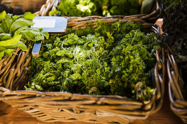 Fresh coriander in wicker basket for sale at supermarket Free Photo