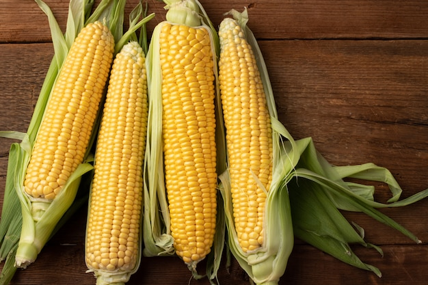 Fresh corn on cobs on rustic wooden table. Premium Photo