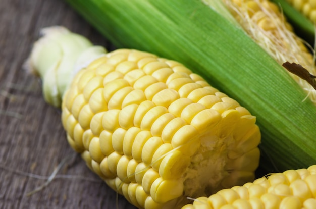 Fresh corn cobs on wooden table. Premium Photo