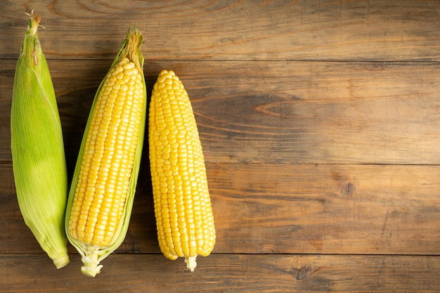 Fresh corn on wooden table. Free Photo