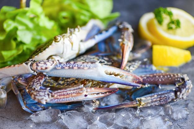 レストランやシーフードマーケットで調理された料理の新鮮なカニ/暗いプレートの背景にレモンとサラダレタスのスパイスと氷の上で生のカニ Premium写真
