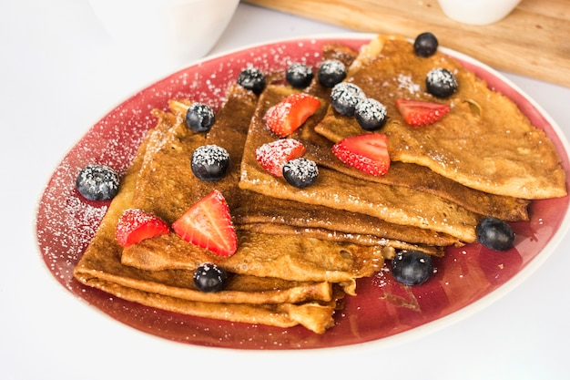 Fresh crepe garnish with strawberries and blueberries on red plate Free Photo