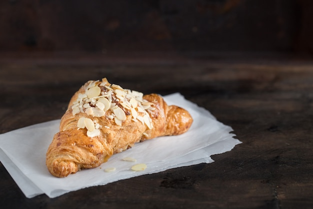Fresh croissant and coffee in a paper cup on dark Premium Photo