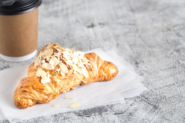 Fresh croissant and coffee in a paper cup on light/ Premium Photo
