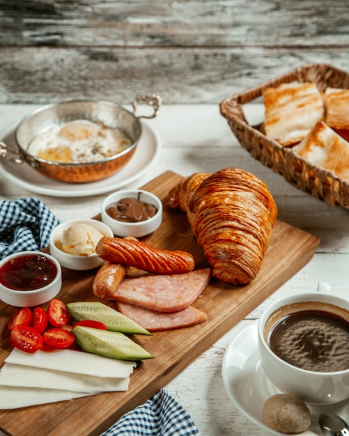 Fresh croissant with fried sausage and cheese Free Photo