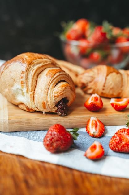Fresh croissant with strawberry jam and strawberry fruit Premium Photo
