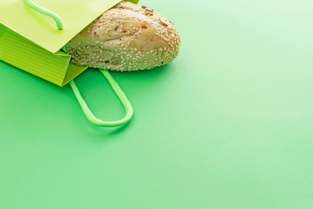 Fresh crusty bread in the shopping bag on a green background. Premium Photo