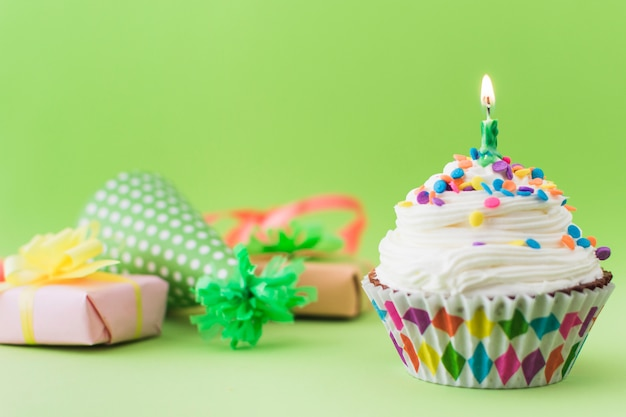 Fresh cupcake with illuminated candle on green surface Free Photo