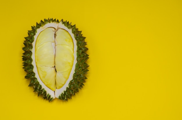 Fresh cut durian which is king of fruit from thailand isolated on yellow background with space for text. Premium Photo