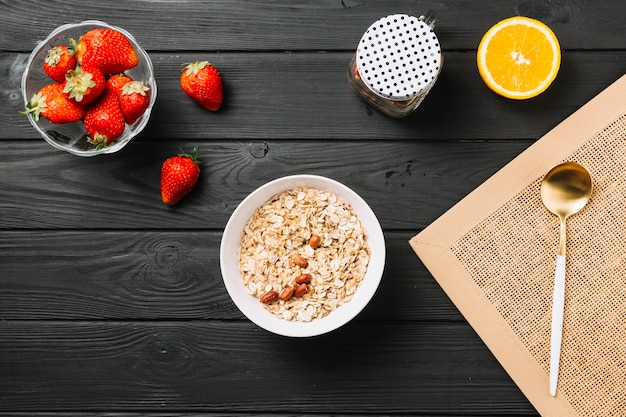 Fresh delicious breakfast with fruits on textured wooden plank Free Photo