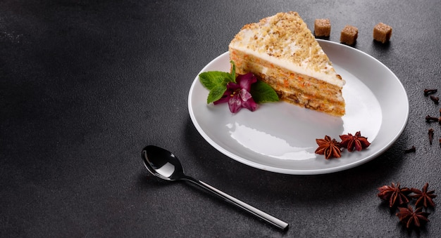 Fresh delicious carrot cake with cream on a dark background. carrot cake with whipped frosting Premium Photo